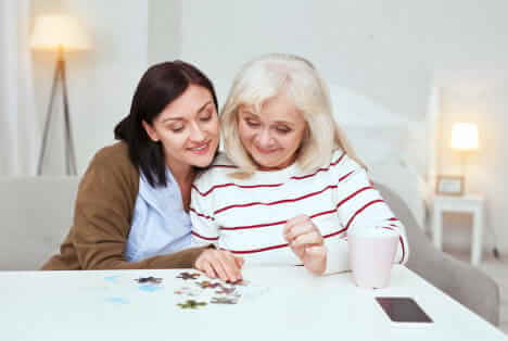 nurse and elder woman playing jigsaw puzzle