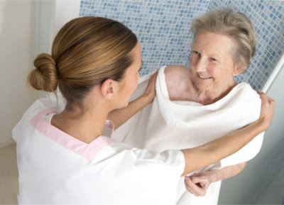 elderly woman taking a bath with her caregiver
